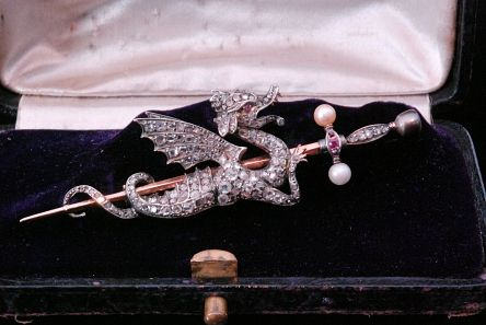 Fieldings Auctioneers | Fine Art, Antiques & Collectables | Stourbridge Hammer price.  £980.00.   A 19th Century diamond, pearl and ruby brooch modelled as a dragon resting upon a sword, the body encrusted with rose cut stones and ruby set eye, terminating in sword handle set with pearls to terminals, length 9cm, all within fitted box.