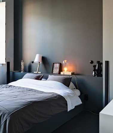 Une tête de lit idéale dans une petite chambre, qui sert aussi de chevet réalisée avec un coffrage bois peint de la même couleur que les murs gris anthracite. Fonctionnelle et facile à intégrer à la déco de la chambre, ce type de tête de lit permet de gagner une place précieuse dans la chambre.