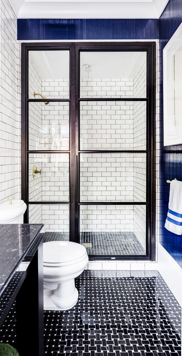 This Gentleman's Bath by Evars + Anderson in the 2015 San Francisco Decorator Showcase features black on white marble basketweave floors, brass fixtures, black grout with white subway tiels and an usual shower door reminisencet of a vintage phone booth.