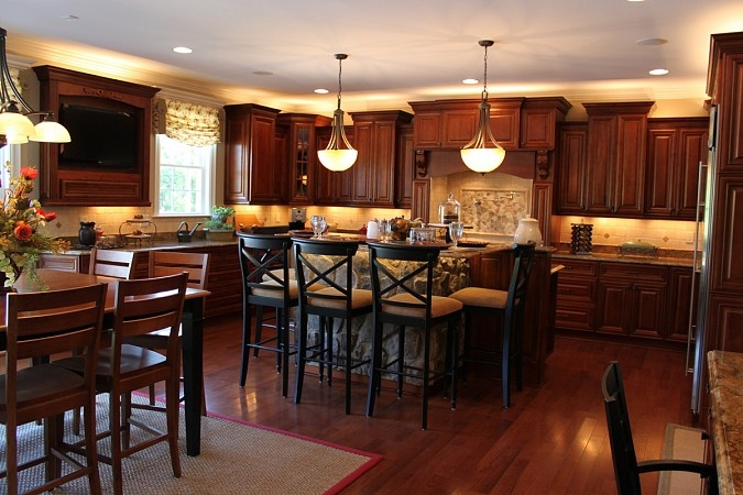 Like the dark cabinets & dark floors. Never would have thought to mount a flat screen in the kitchen like that!