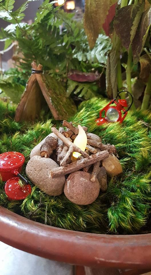 Flickering Fire Pit Miniature perfect for your fairy garden, gnome garden, or miniature garden! The fire pit features rocks around the perimeter and real wood b