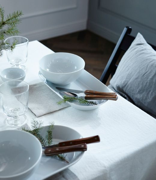 Want to win a few wows with your table setting? Try place settings that fit in a theme. We've used light colored textiles and dinnerware with evergreen pine branches.