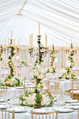 gorgeous floral and candelabra centerpieces! - I think this could be done in a smaller way using a tall heavy candlestick with greenery traveling up to the top.