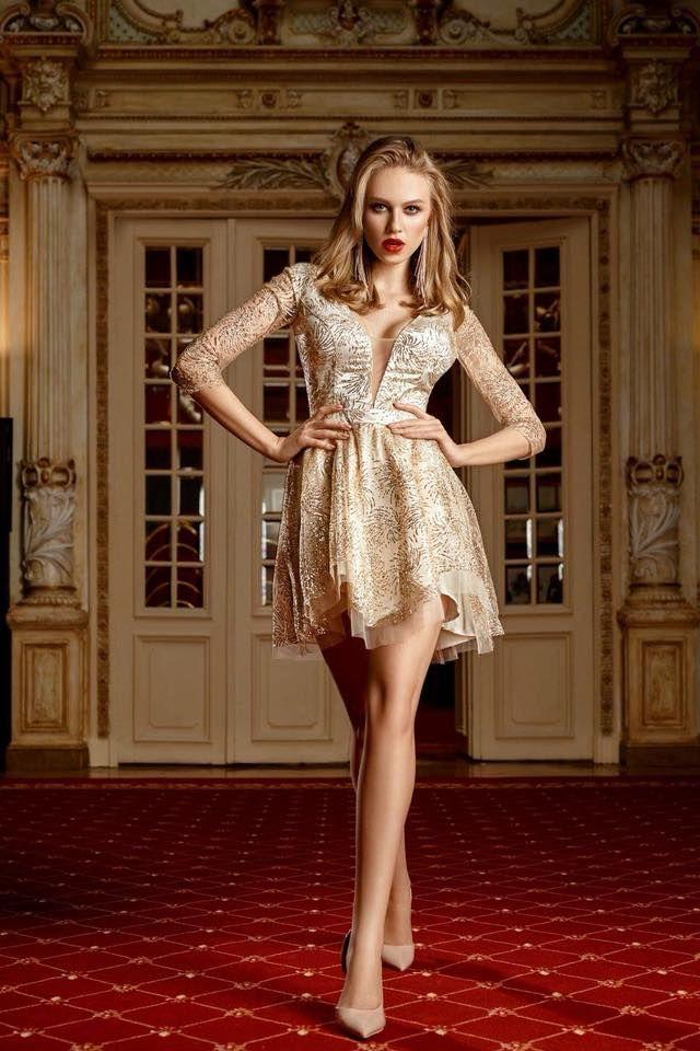 """O rochie printesa nu se va demoda niciodata deoarece cofera un simt fin al frumusetii feminine purtatoarei ei! De aceea, pentru Revelion sau Craciun alege o rochie tip princess MINI aurie cu dantela si sclipici, top cu cupe push-up si decolteu adanc in """"V"""", maneci trei sferturi din tul cu dantela cu sclipici si o fusta ampla cu volane. Talia marcata va sublinia silueta ta armonioasa si transparenta de pe spate te va propulsa in Regina Serii."""
