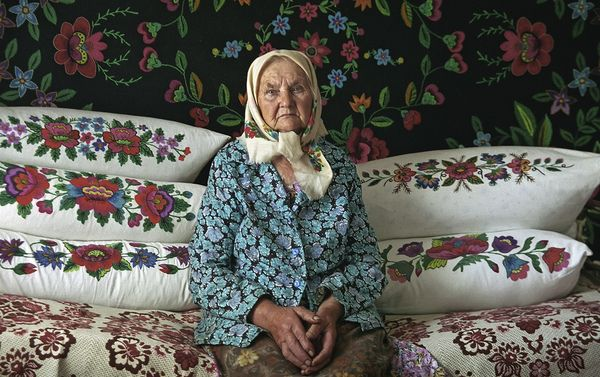 Woman, Ukraine, photo BY: Vladimir Kukorenchuk  .... those are down pillows behind the Ukrainian woman..  most likely she did all that embroidery work
