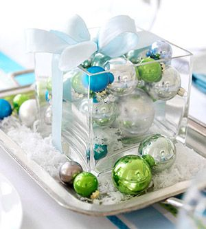 """Served-up centerpiece - To make a showy centerpiece, place solid-color ball ornaments inside a clear-glass vase and """"serve"""" on a silver tray. Sprinkle faux snow over the display, and wrap it up with matching ribbon."""