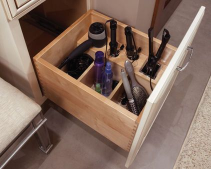 Curling irons, hair dryers and brushes take up a lot of space and are easily tangled. I love this idea of having sectioned storage for each item within the same cabinet. If hiring a cabinet maker to retrofit your existing drawer to look something like the one shown here isn't in your budget, try using plastic boxes within the drawer to get the same functionality.