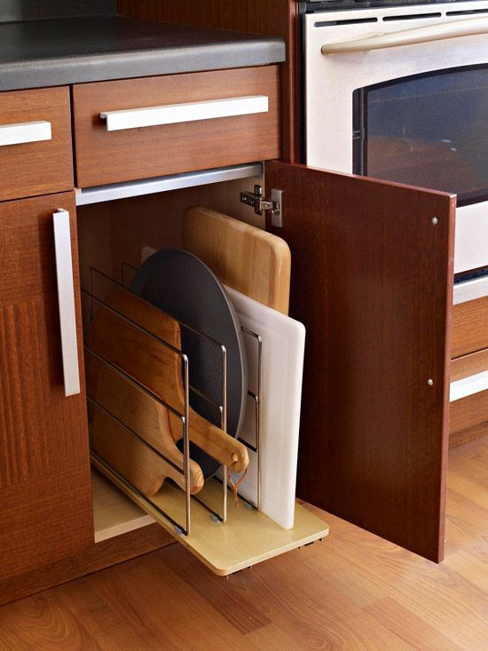 Store shallow items, such as cutting boards and platters, upright. Even narrow spaces next to your range or your sink can be used in this manner. Use dividers to separate items for easier retrieval.