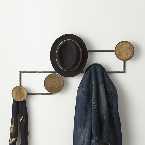 Playful asymmetry and a modern mix of metals allow this eclectic coat rack to double as modern wall art.