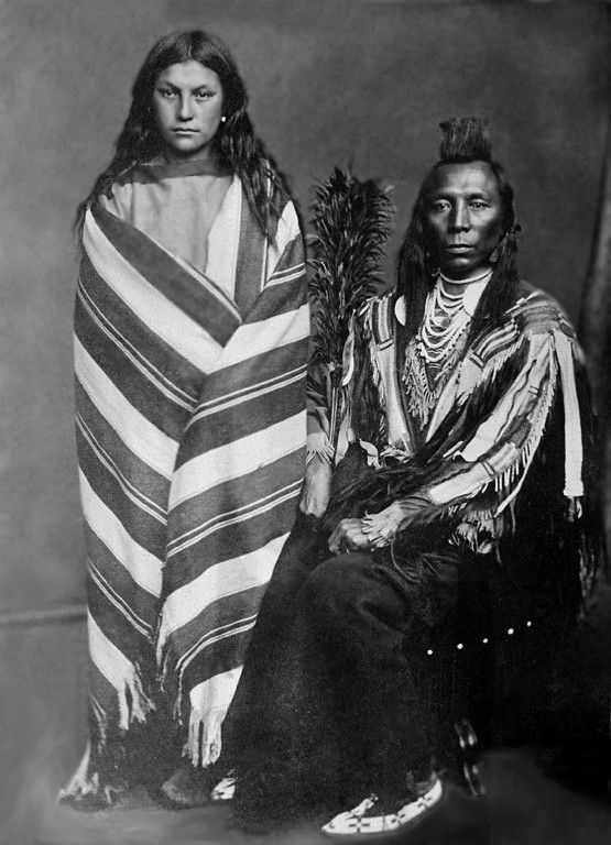 A Crow husband and wife. Old Crow and Pretty Medicine Pipe. Photo taken 1873.                                                                                                                                                                                 More