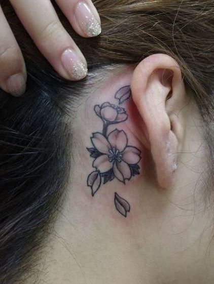 Piccolo tatuaggio fiori di ciliegio dietro orecchio