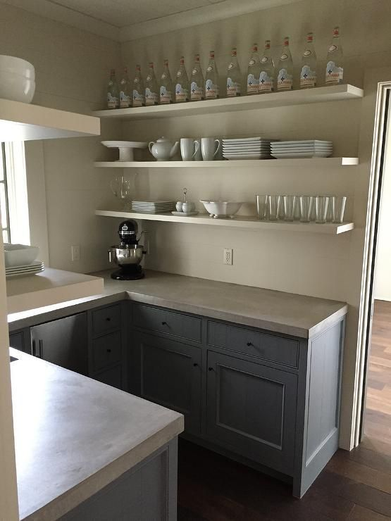 Amazing U shaped butler's pantry features gray cabinets fitted with a stainless steel mini fridge paired with concrete countertops situated under floating shelves.