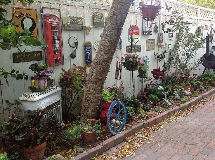Garden whimsey - look at all these eclectic treasures on the fence!