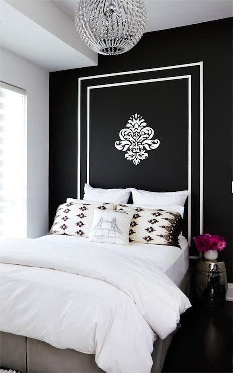 """""""Stacey Cohen – Gorgeous bold black accent wall with white painted frame headboard, silver garden stool, crystal chandelier, gray bed skirt and crisp white bedding."""""""