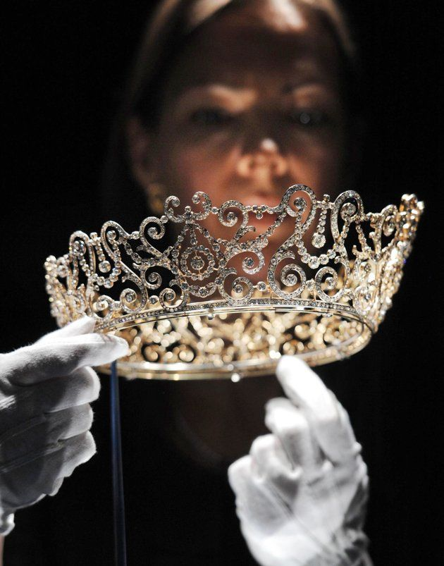 This photo shows curator Caroline de Guitaut, holding the Delhi Durbar Tiara, on show for the first time and made to mark the succession of King George V as King Emperor in 1911, at a new exhibition at Buckingham Palace, London. The new exhibition at Buckingham Palace shows jewels collected by six monarchs over three centuries to mark the Queen's Diamond jubilee this summer.