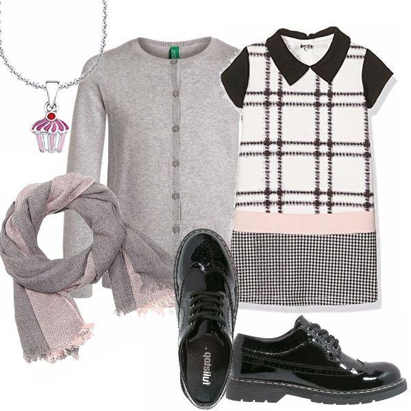 Vestino in fantasia a righe e a quadretti, manica corta, collettino a punta nero. Cardigan scollo tondo grigio. Stringata in vernice nera. Sciarpina rosa e grigia. Collana con ciondolo.