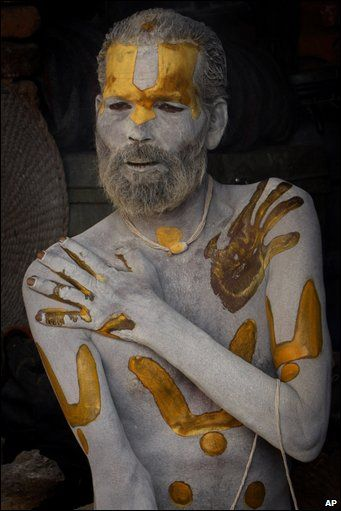 A sadhu applies ash and colored paste to himself at the Pashupatinath temple in Kathmandu, Nepal.