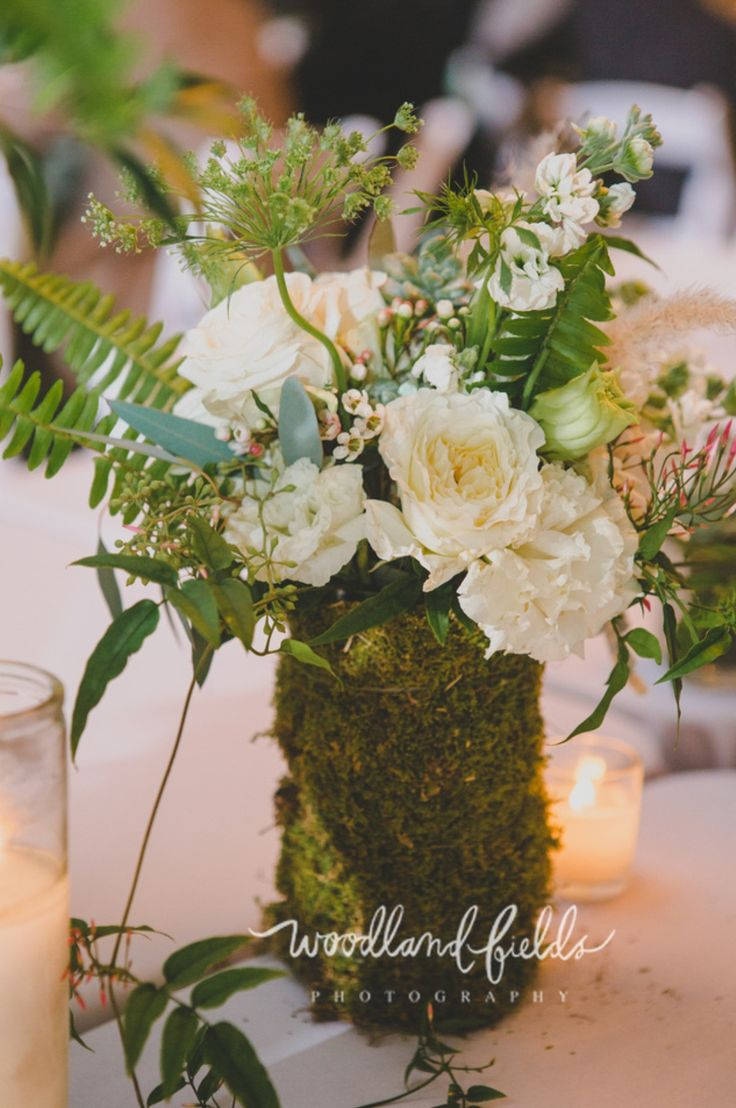 a mossed vase on the head table provided the perfect spot to repurpose the bridesmaids bouquets made of vendela roses, white stock, white lisianthus, white queen anne's lace, seeded eucalyptus, dusty miller, fern, jasmine trails, white fountain grass, and succulents wrapped in cream satin ribbon