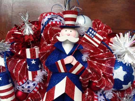 This 24 inch deluxe red and white popcorn mesh has a patriotic Uncle Sam waving the American flag in the center surrounded with decorative balls, hand painted star balls, glitter stars and glitter picks with patriotic ribbon and glitter roping all through the wreath.