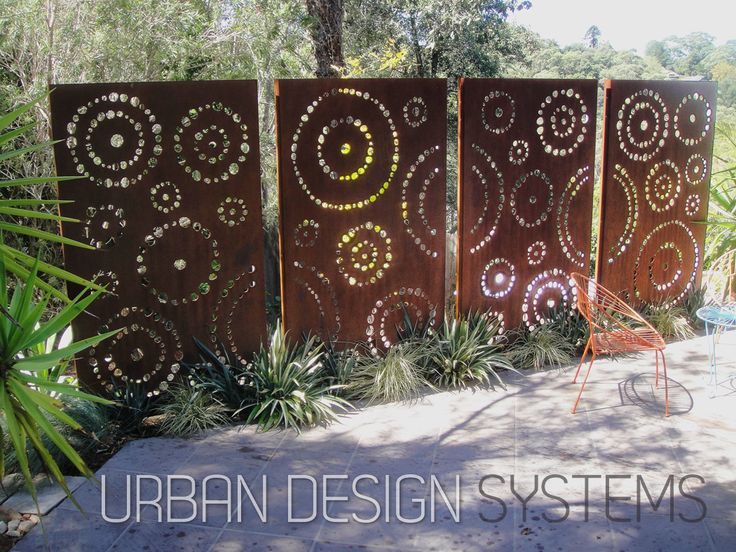 Laser cut screening - Dots (custom)  This stunning four panel feature wall is made of corten weathering steel. Each panel is independently installed on hidden steel posts concreted in-ground, leaving a precision gap between each panel. The striking feature wall cleverly screens off a service area for the garden.