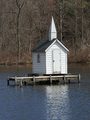 "World's Smallest Church; Oneida, NY-  Cross Island Chapel, sits on a wooden platform in the center of a pond, accessible only by boat. A billboard near the road details everything you need to know: ""Built in 1989. Floor area 51 inches by 81 inches (28.68 square feet). Seats two people. Non-denominational. Dedicated as a witness to God."""