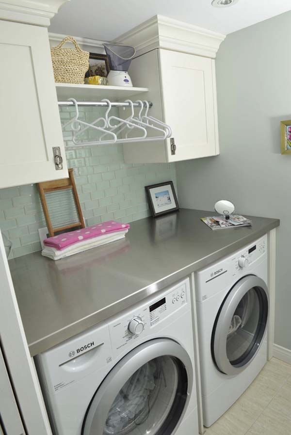 Small Laundry Room Design Ideas-30-1 Kindesign-- I like the cabinets on either size with the towel bar in the middle to hang stuff on