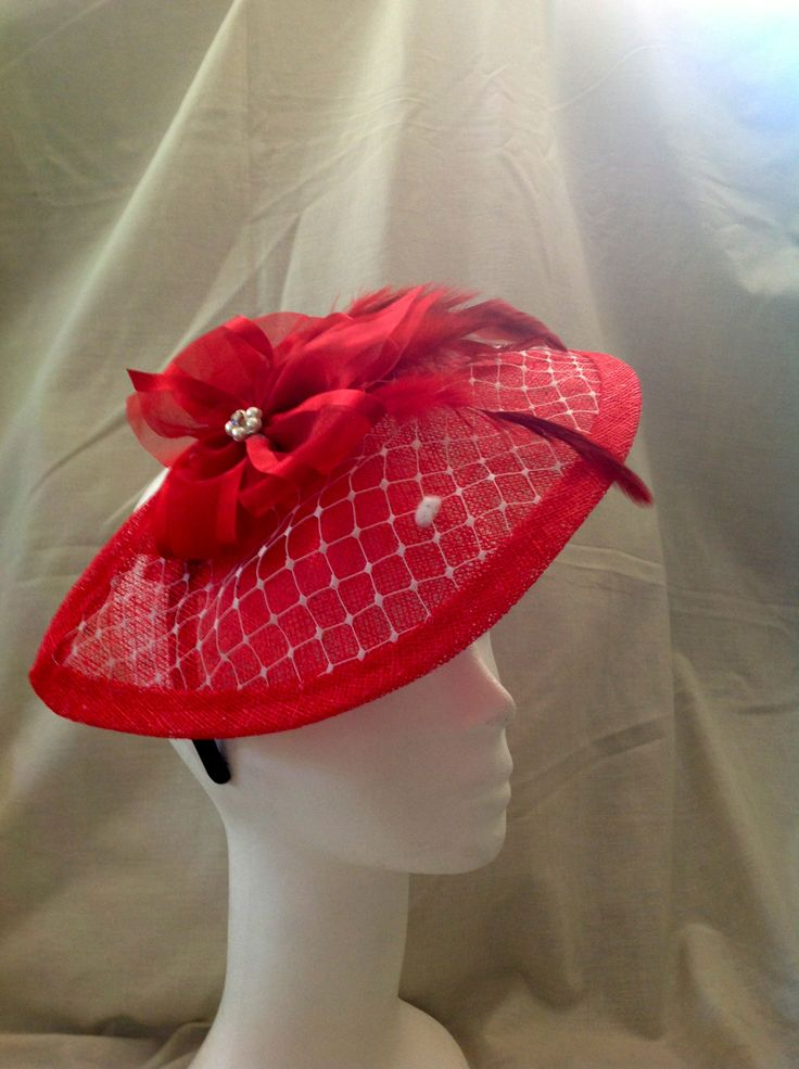 The Madeline is a large fascinator on a black head band the base is ruby sinamay in a half moon shape covered with white netting and the centre piece is a large ruby flower with pearl and diamante detailing and matching feathers to finish. $130 AUD.