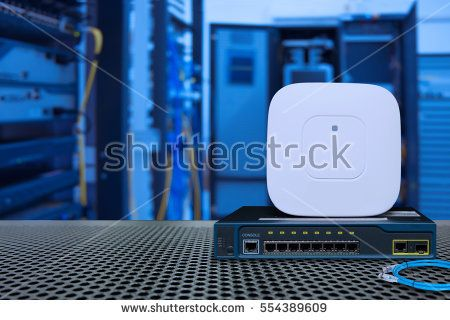 Network switch gigabit port utp and sfp and wireless access point for high speed network on Table mesh in front of rack data and communication server and blur background.