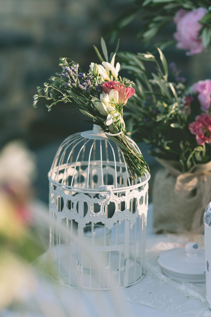 Vintage white bird cages, were a beautiful medium to show off the elegant flower bouquets. #birdcage #white #vintage #flowers #elegant #decoration #weddingplanner #dreamsinstyle