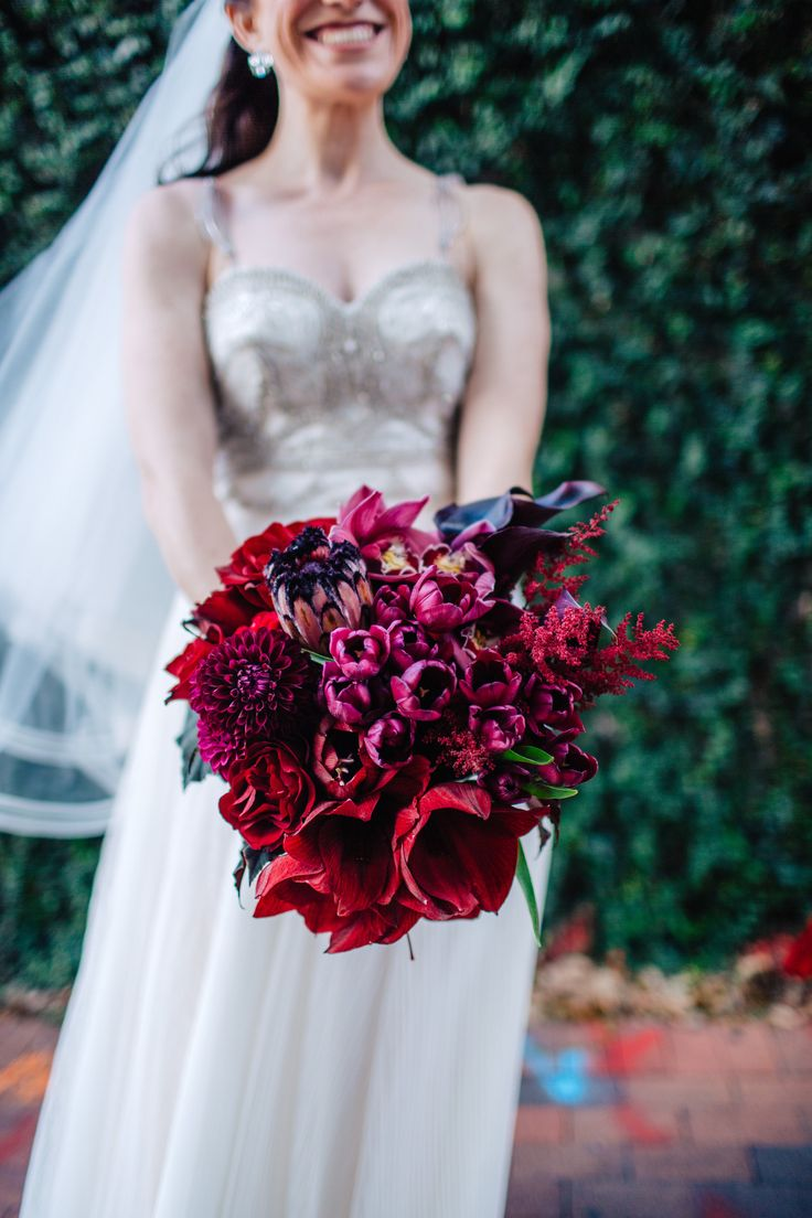 modern and glamorous bridal bouquet of red amaryllis, burgundy mini calla lily, black parrot tulips, burgundy astilbe, deep red roses, chocolate cymbidium orchids and pink mink protea and burgundy dahlias and begonia leaf.