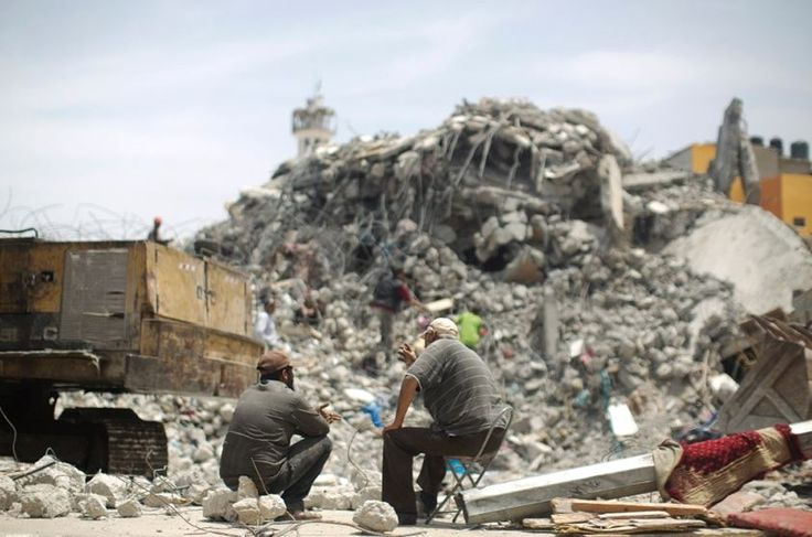 Palestinian men sit amid the rubble of houses destroyed during the 50-day war between Israel and Hamas militants in the summer of 2014, in the Eastern Gaza City Shujaiya neighbourhood
