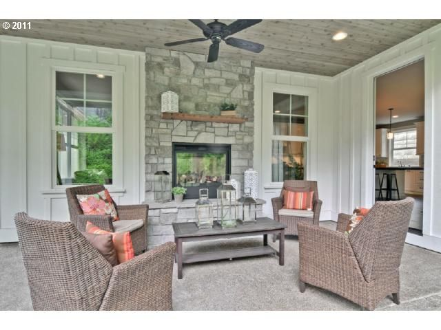 Indoor Outdoor Fireplace in cute covered porch with paneled walls and ceiling - Estately
