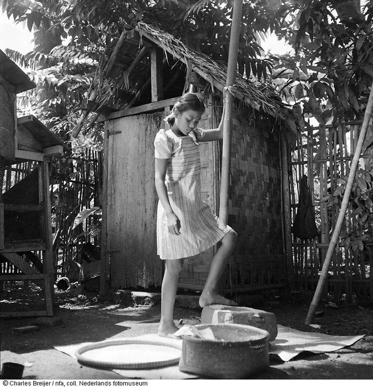 Een meisje breekt rijst in een vijzel op een achterplaatsje voor de familie Muljono te Jakarta, Indonesië (1949)