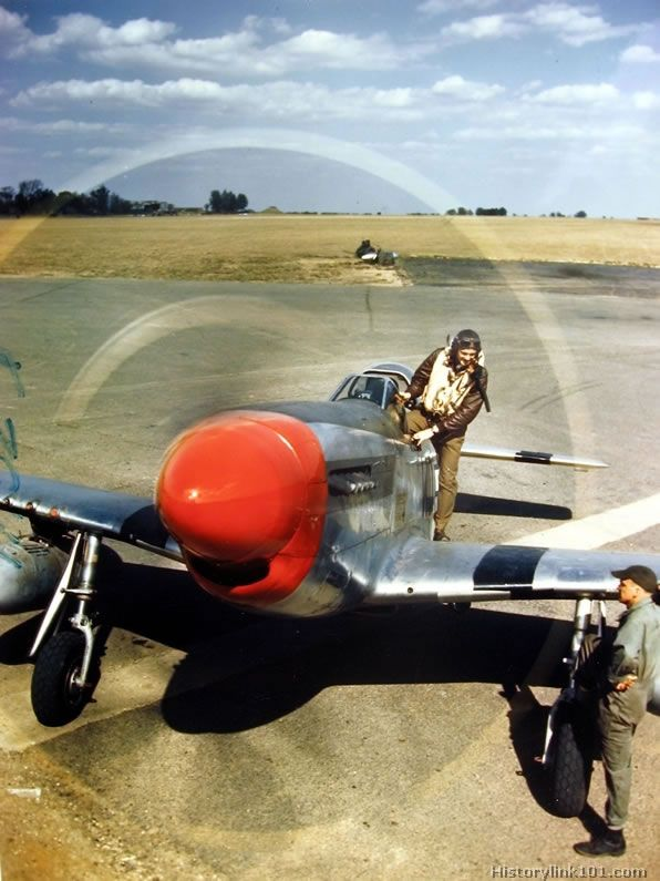 Pilot standing on the wing of his P-51 Mustang, ready to get into the cockpit. His crew chief stands by.