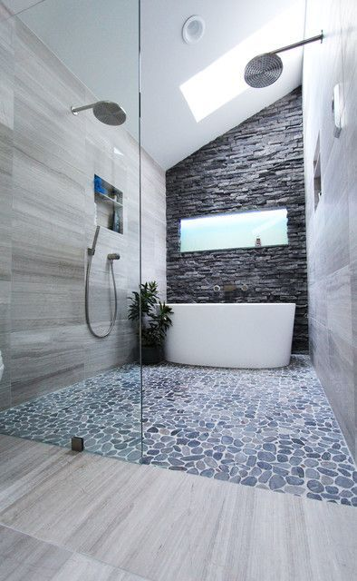 A closer look at the shower and tub enclosure reveals a curbless shower with a pebble floor, a Victoria and Albert tub, and a stacked stone wall at the far end of the enclosure.