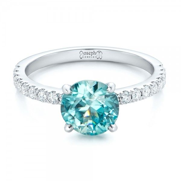 #102318 This lovely engagement ring features a round blue zircon in the center, accented with diamonds running down both shank shoulders, and all set in white gold. It was...