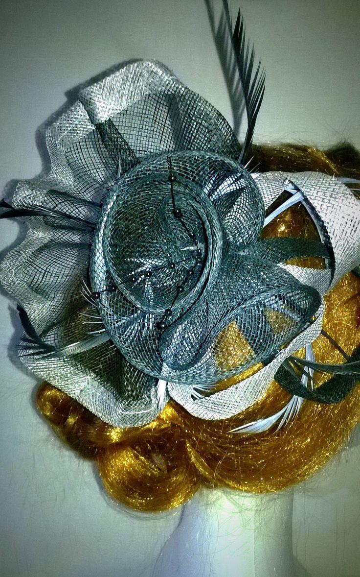 Fiore realizzato in sinamay con piume, può essere usato sia come accessorio per capelli che come spilla