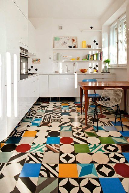 Polish cement tile patchwork floor adds color and movement to a white kitchen.