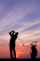 Silhouettes of a golfer golfing against colorful sunset illustration
