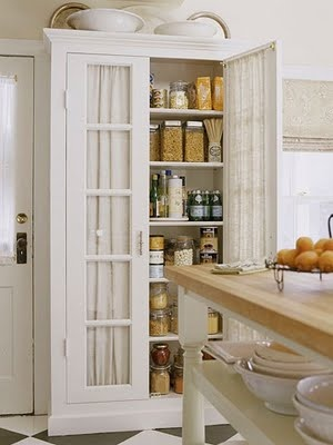 Add a pantry...glass doors with a curtain for pantry doors.  This could work