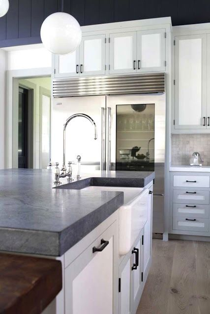 the kitchen island features gray soapstone counters and white cabinet doors framed in a light gray