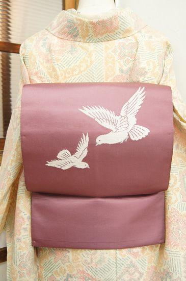 グレーがかった、ほのかに藤色をおびた薄紅色の地に、白い二羽の鳩が織り出された開き名古屋帯です。