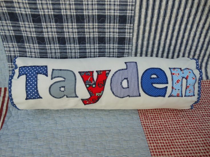 A bolster cushion with appliqued name for a baby boy.