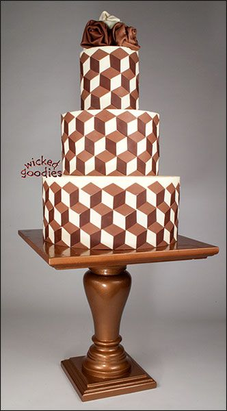 This tutorial demonstrates how to make an optical illusion cake using three different tones of rolled modeling chocolate. This is a 2-dimensional design that gives the impression of 3-dimensional cubes