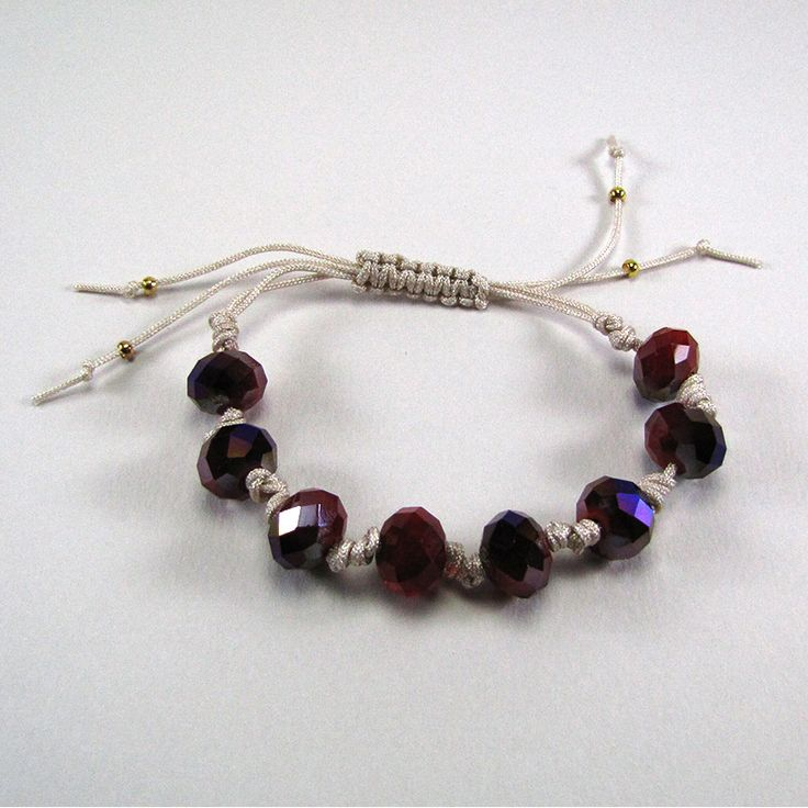 Adjustable bracelet with beige cord and red-purple glass beads.
