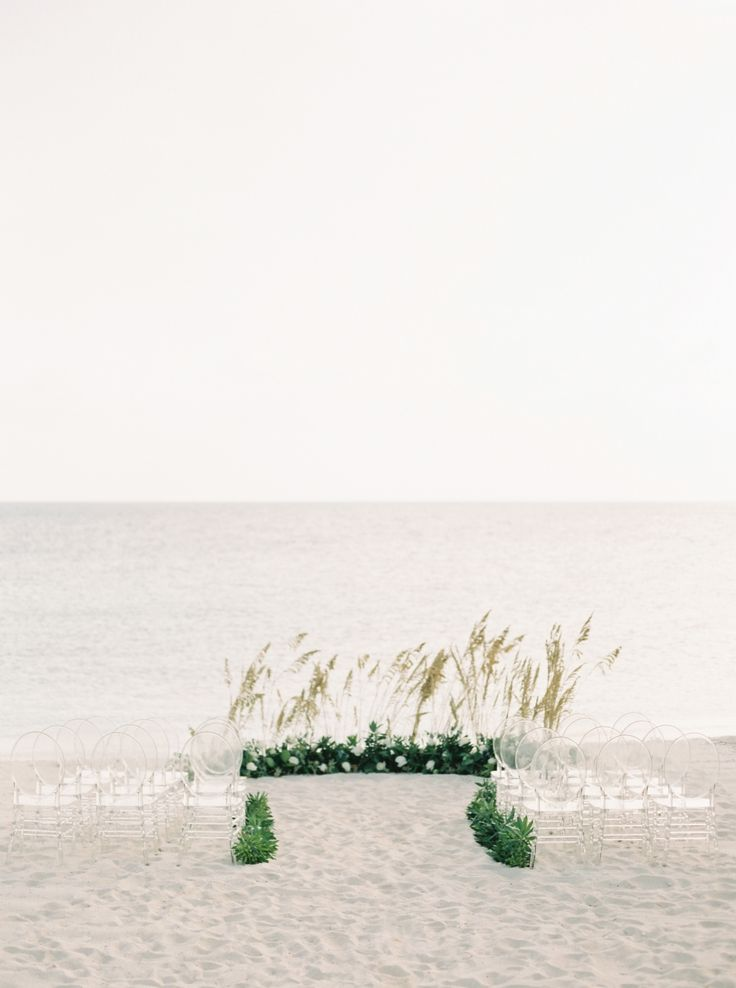 beach wedding ceremony lucite chairs sea oats | Photography: Simply Sarah