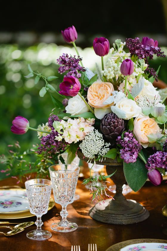 Light purple tulips and dark purple artichokes in this gorgeous centerpiece by Botanica Floral & Event Design.