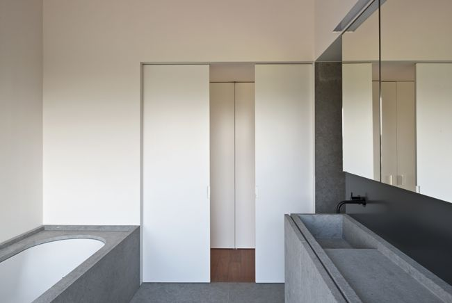 Muted gray and white bathroom in Vincent Van Duysen's DC II Residence. Photography by Koen van Damme