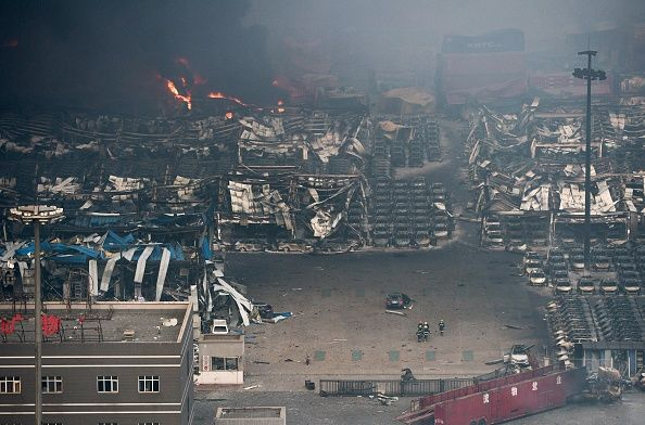 Fire and smoke rise at the site of the massive explosions in Tianjin on August 13, 2015.  Enormous explosions in a major Chinese port city killed at least 44 people and injured more than 500, state media reported on August 13, leaving a devastated industrial landscape of incinerated cars, toppled shipping containers and burnt-out buildings. (Photo credit: STR/AFP/Getty Images)