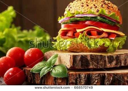 Вкусный ветчиной, сыром и салями сэндвич с овощами, листьями салата, помидорами Черри в естественной обстановке с деревянной фоне